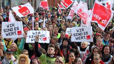 """ver.di Warnstreikkundgebung mit Personen, Fahnen und dem Plakat """"Wir sind es Wert!"""""""