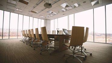Ein Konferenzraum mit Tisch und unbesetzten Stühlen.