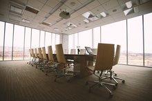 Ein Konferenzraum mit Tisch und darum unbesetzte Stühle.