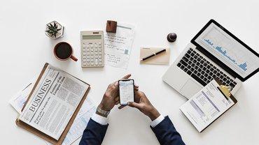 Eine Hand mit Handy sowie ein Schreibtisch mit verschiedenen Arbeitsmitteln wie Laptop, Zeitung, Stifte, Block usw.