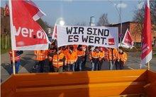 """mehrere Straßenwärter*innen und das ver.di - Transparent """"wir sind es wert!"""