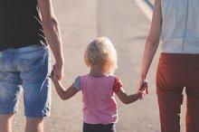 Ein Kind, welches rechts und links von den Eltern an der Hand gehalten wird.
