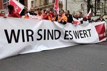 """Ein Transparent mit der Aufschrift """"Wir sind es wert!"""", verschiedene ver.di-Fahnen; Personen."""
