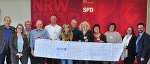 Pflegebeschäftigte in der Justiz mit einer Unterschriftenliste