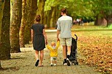 Eine Familie läuft einen Parkweg entlang