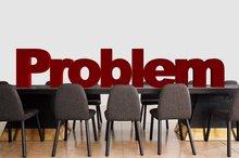 """Ein Tisch mit leeren Stühlen darum und auf dem Tisch steht das Wort """"Problem""""."""