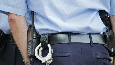Ein Polizist von hinten, Funkgerät und Handschellen sowie Pistole sind erkennbar.