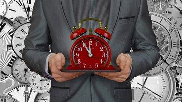 Ein Mensch im Anzug hält eine Uhr in das Bild