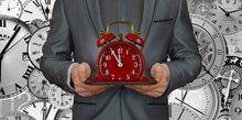 Ein Mensch hält eine Uhr in das Bild