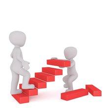 Eine Person geht eine Treppe hoch, deren Stufen von einer anderen Person ergänzt werden.