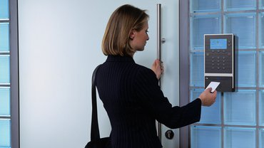 Eine Frau steht vor einem Zeiterfassungsgerät und öffnet eine Türe.