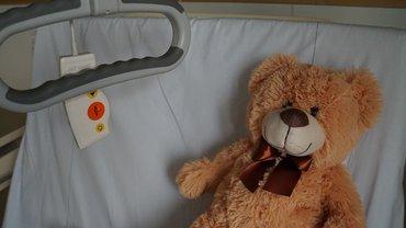 Ein Teddybär in einem Krankenhausbett.