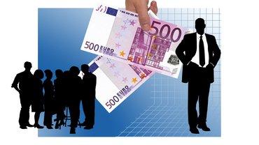 Zwei Fünfhunder-Euro-Scheine und eine Gruppe Beschäftigter.